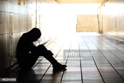 Teenager depressed sitting inside a dirty tunnel : Stock Photo