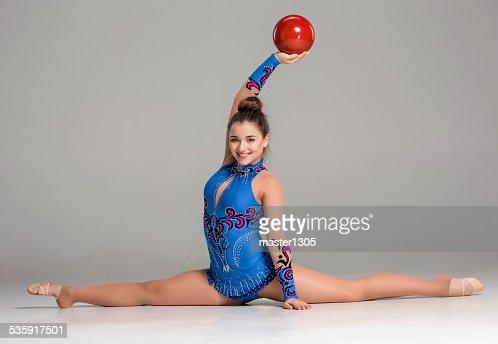 teenager doing gymnastics exercises with red gymnastic ball : Stock Photo