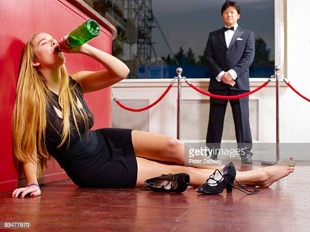 Teenager drinking Champagne on nightclub floor