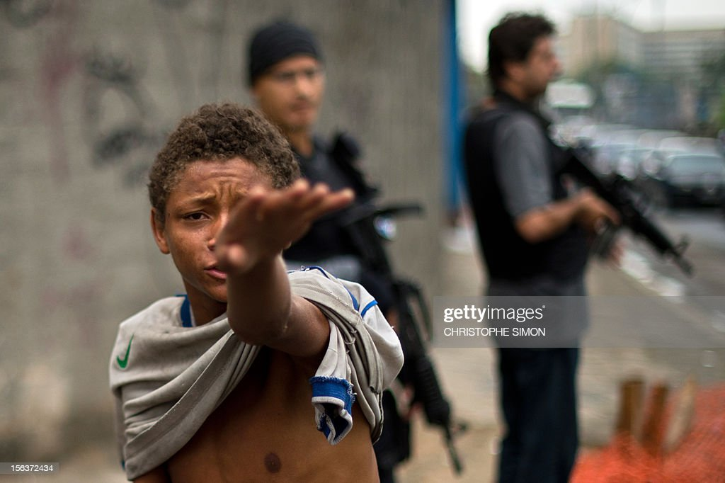 A teenager gestures after being caught by social workers next to Parque Uniao slum during an operation to retire crack addicts from the streets in Rio de Janeiro on November 14, 2012.