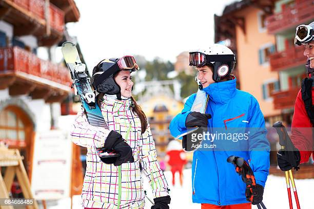 Teenager girl and boy, carrying skis