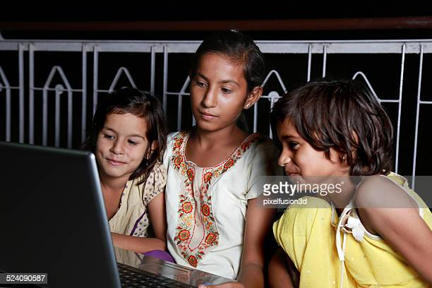 Teenager Girl Holding Laptop with Her Sisters