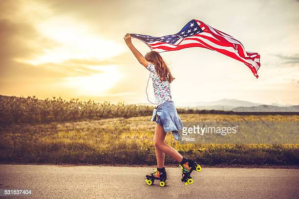 Teenager girl holds an American flag and roller skating