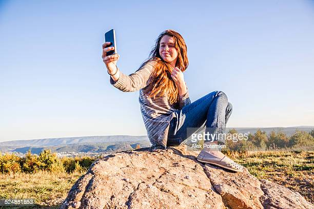 Rapariga adolescente tirar uma Selfie no topo da montanha