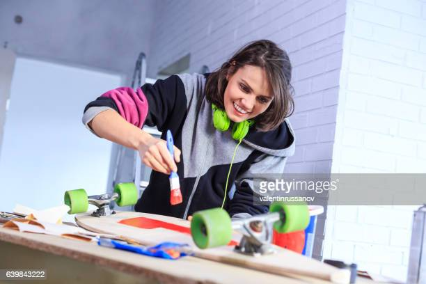 Teenager girl painting a skateboard