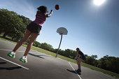 Teenager Girl Shooting Basket in Summer Outdoor Basketball Game