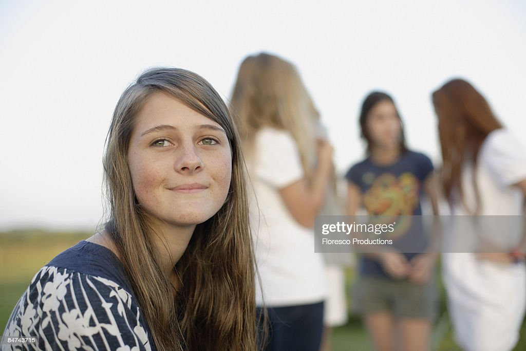 Teenager girl sitting in front of socializing friends : Stock Photo