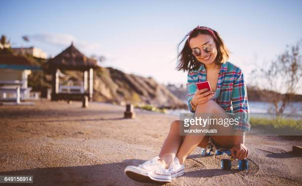 Teenager girl skateboarder using smart phone next to the sea