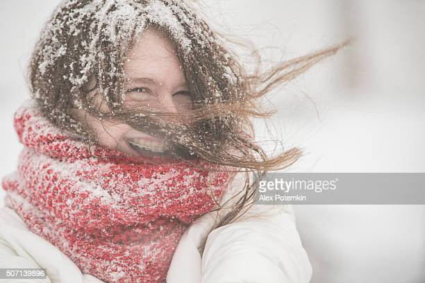 Teenager girl under snowfall at the street