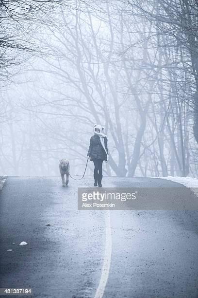Teenager girl walking dog in the haze