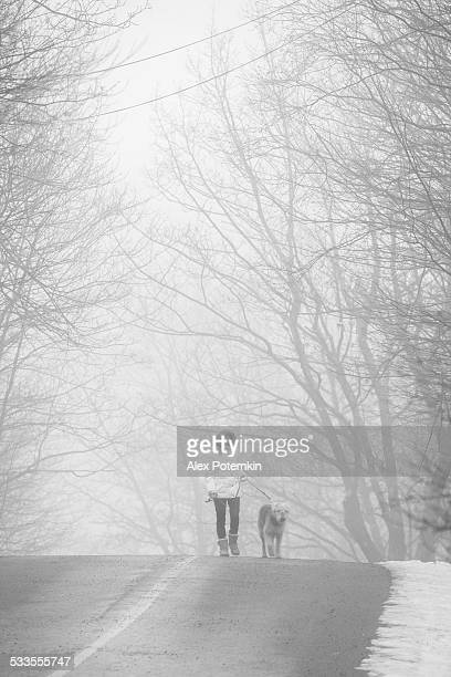 Teenager girl walking dog in the haze