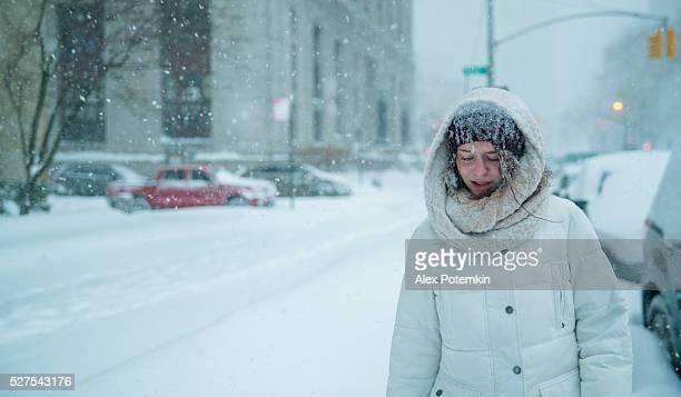 Teenager-Mädchen geht unter Schneefall auf der Straße in Manhattan
