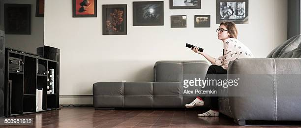 Teenager girl with a TV remote control
