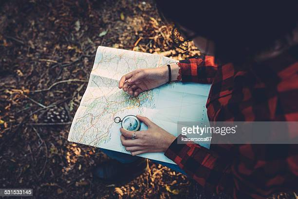 Teenager girl with Compass Reading a Map in the forest