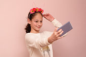Teenager girl with diadem of flowers taking selfie with her cell phone.Close-up portrait of a young smiling pretty child wearing Springtime Fairy Costume or Flower Crowns at Shavuot.