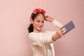 Teenager girl with diadem of flowers taking selfie with her cell phone.Close-up portrait of a young smiling pretty child wearing flower diadem taking a photo of herself with phone on pink background.