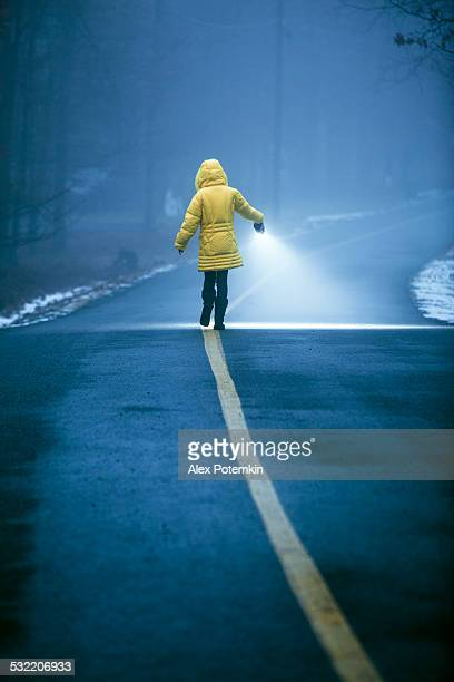 Teenager girl with flashlights walking in the haze