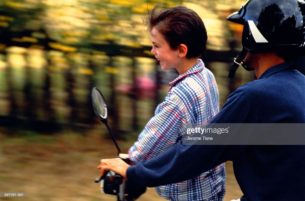 Teenager giving boy (3-5) ride on moped, blurred motion : Stock Photo
