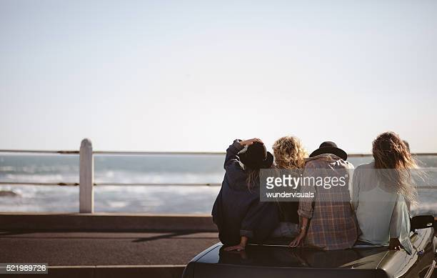 Teenager hipster styled friends watching the sea from their conv