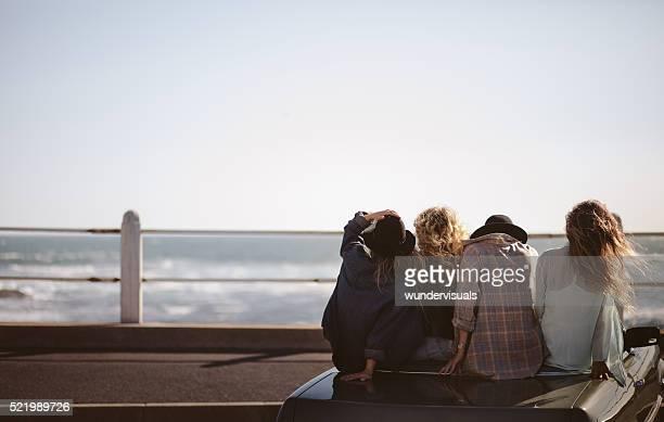 Adolescente hipster creato amici guardando il mare dal loro congressi