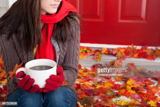 Teenager holding coffee mug at front steps