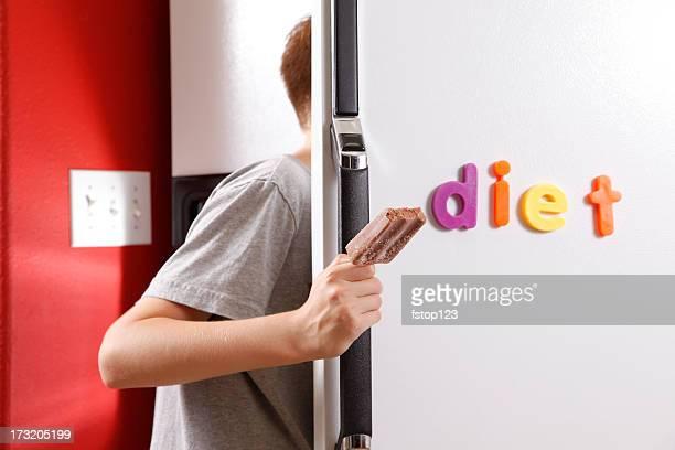 Teenager holding fudge bar looking in refrigerator DIET sign