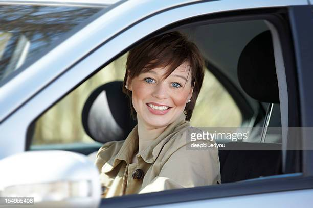 teenager in a car smiling at camera