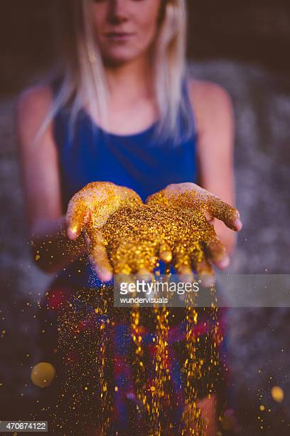 Teenager in blue with gold glitter falling from her hands