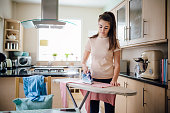Teenage girl ironing laundry in the kitchen.