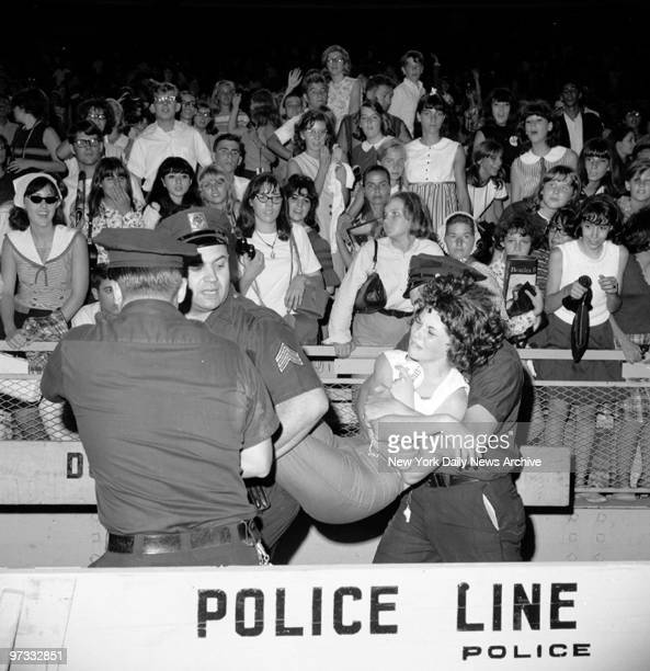Teenager is carried off during the Beatles concert at Shea Stadium
