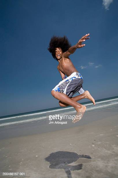 Teenager (13-15) jumping in air on beach, side view