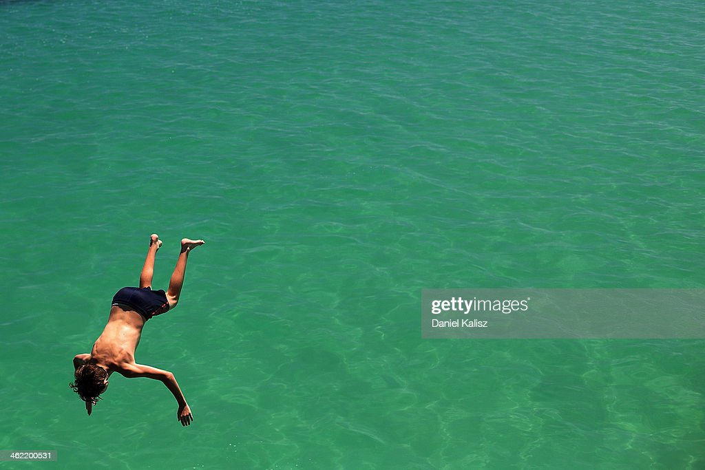 A teenager jumps from the jetty during a heat wave at Glenelg beach on January 13, 2014 in Adelaide, Australia. Temperatures are expected to be over 40 degrees celsius all week with health authorities warning the young and elderly to remain indoors.