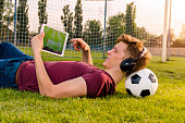 Teenager laying on grass with soccer ball behind his neck , watching soccer game on tablet
