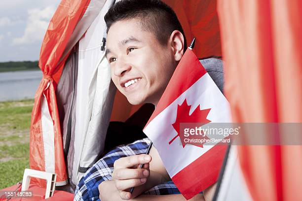 Teenager laying while holding the Canada flag