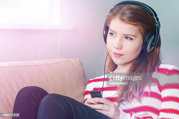Adolescente escucha música a través de auriculares