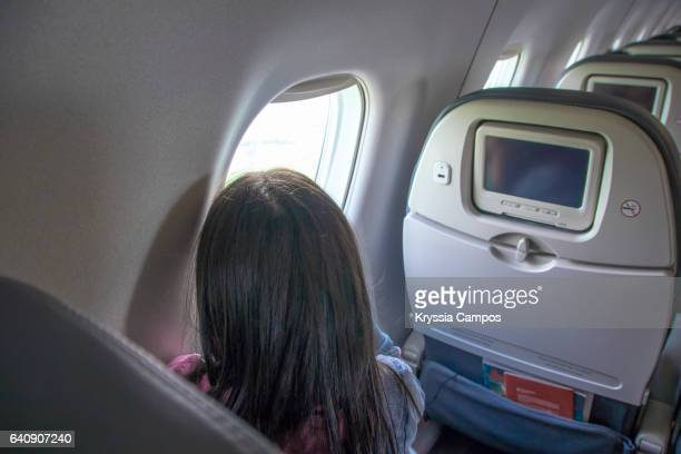 Teenager looking at the view on airplane window