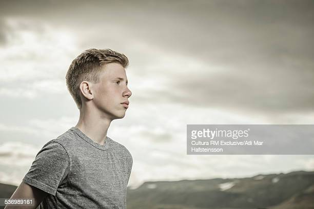 Teenager looking serious, mountain range in background