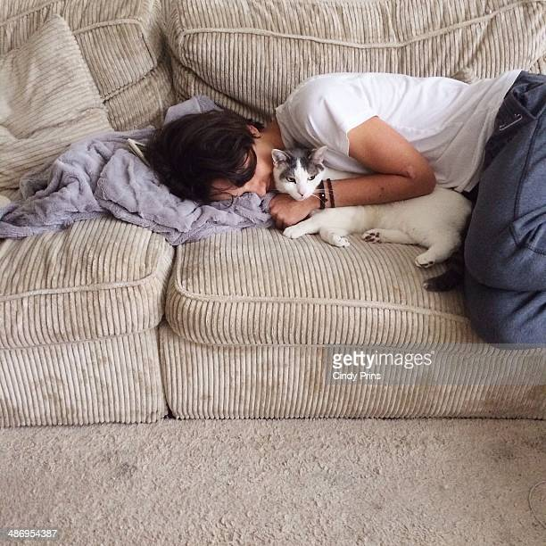 Teenager lounging on the couch and cuddling his cat