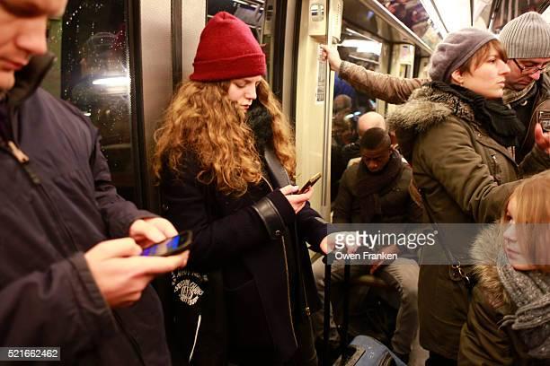 teenager on her smartphone on the Paris metro