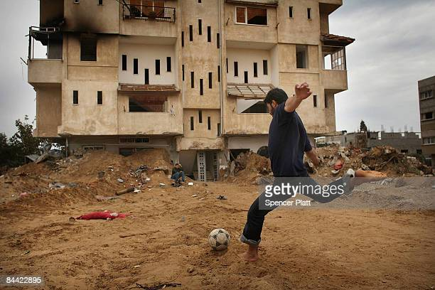 A teenager plays a game of soccer with friends in front of his damaged apartment building on January 23 2009 in a heavily damaged suburb in Gaza City...