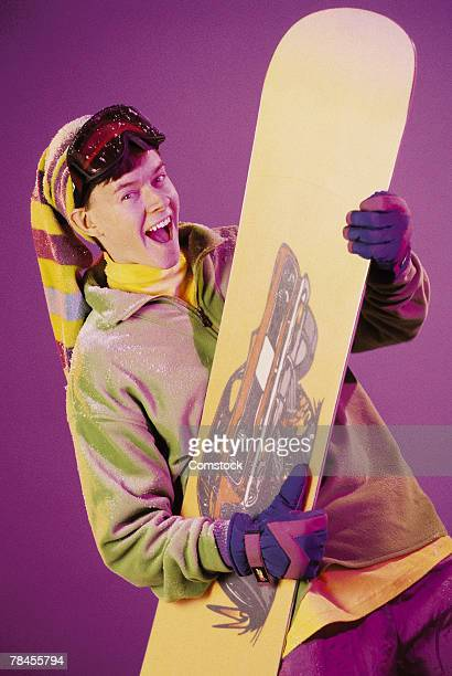 Teenager posing with snowboard