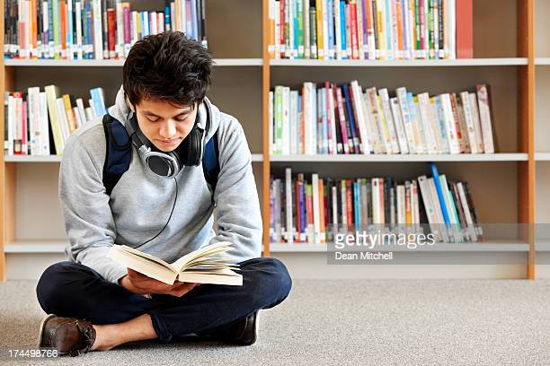 Teenager reading a book in the library