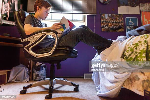 Teenager reading magazine at home