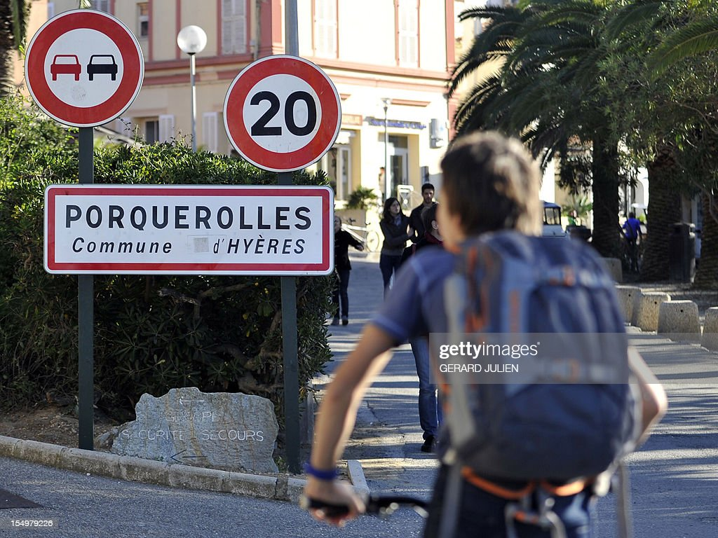 A teenager rides his bike past a road sign on October 29, 2012 as he takes part in the search for a 12-year-old British boy, who disappeared on October 27, on Porquerolles island, southeastern France. Sixty soldiers and three civil security dog-handlers from Brignoles are paricipating in the search.