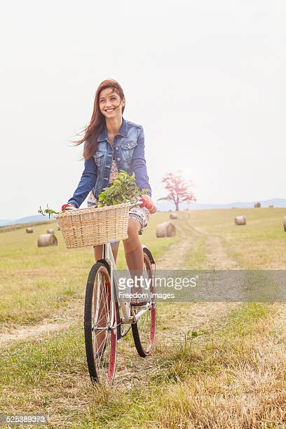 Teenager riding bicycle on field, Roznov, Czech Republic