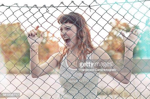 Teenager screams behind a wire mesh