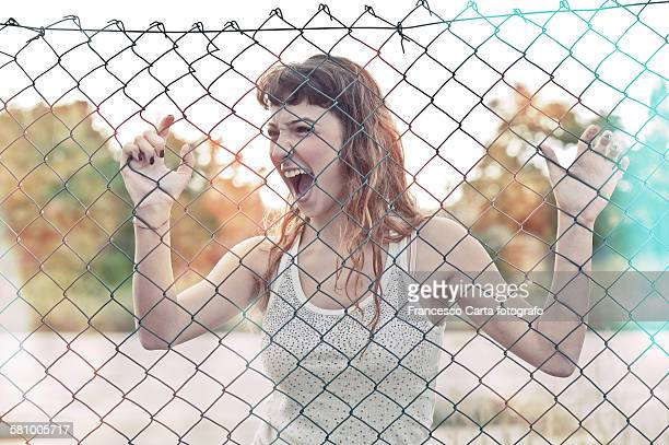 Teenager screams behind a wire mesh