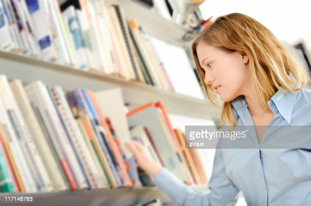 Teenager searching a book in the library