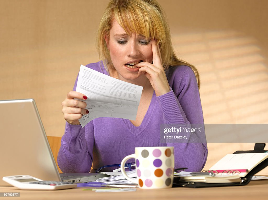 Teenager showing anxiety holding bill : Stock Photo