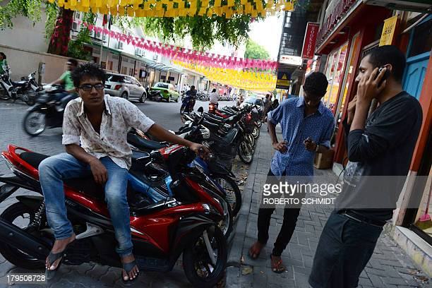 A teenager sits on a moped as he hangs out with some of his friends at a corner of a street in Male capital of Maldives on September 4 2013 Male is a...